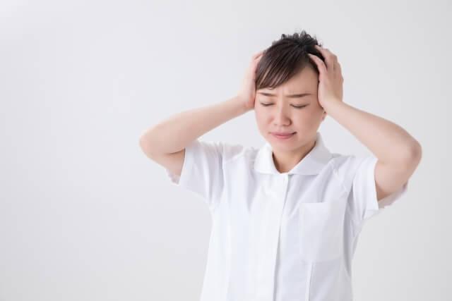頭を抱えている女性介護士