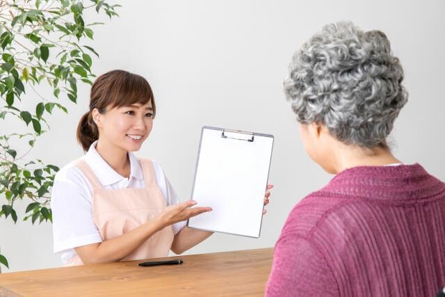 高齢者に説明している女性介護士