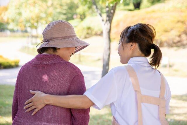 高齢女性の肩を抱く女性介護士