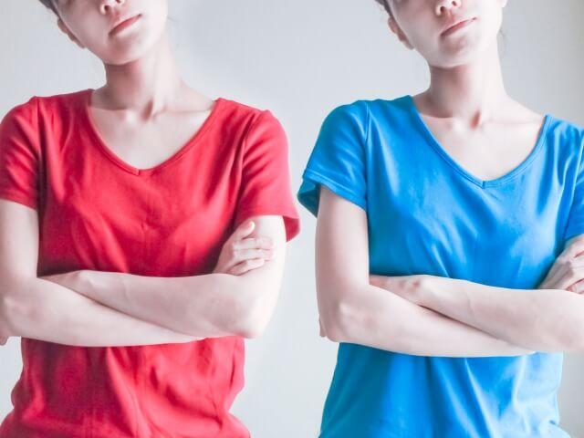 赤い服の女性と青い服の女性が腕組みをしている